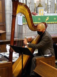 Harper Kirk playing the harp at St. John's with a mask during a service with COVID precautions..